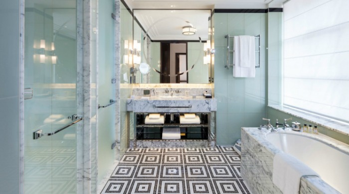The Beaumont Hotel, London: A bathroom in one of the rooms with black and white patterned floor tiles and marble details.
