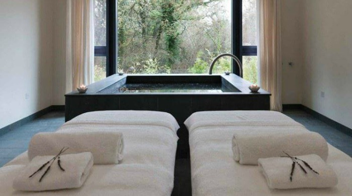 Five of the Best UK Spas: A treatment room at Lime Wood Hotel with massage tables and a square bath.