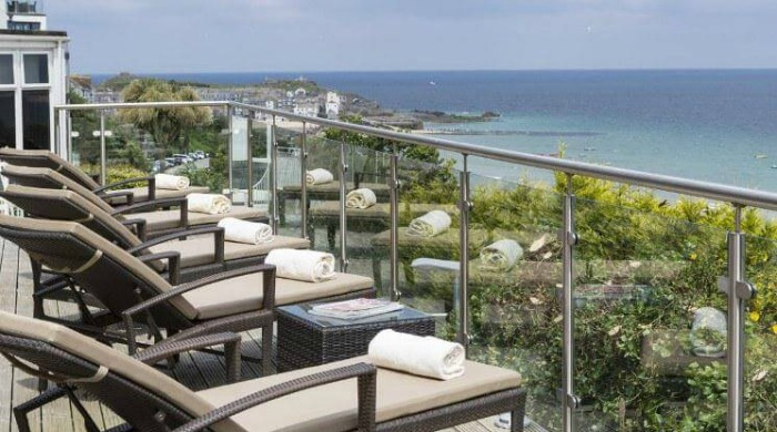 Five of the Best UK Spas: A balcony filled with deck chairs overlooking the sea at St Ives Harbour Hotel.