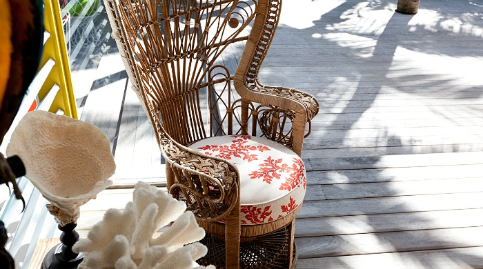 La Banane: An ornate ricker chair with decorative sea coral on a sunny decking.