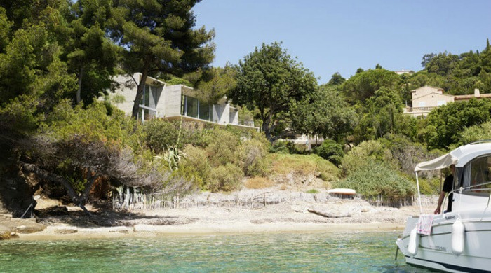 A view of the Maison le Cap from the nearby sea with a view of the beach and surrounding trees.