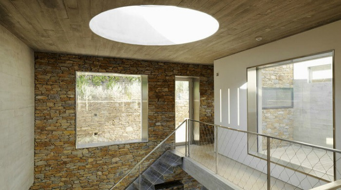 An interior shot of the Maison le Cap featuring a rustic stone wall, a large, circular skylight, a metallic staircase and large, square glass windows.