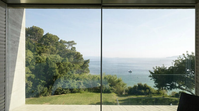 A view of the trees and ocean from the large, square windows of the Maison le Cap.