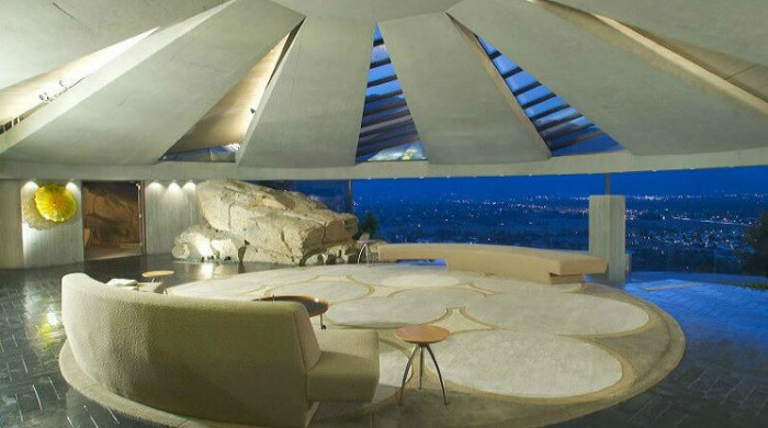 An open living in the Elrod House which looks onto a view of Palm Springs lit up at night.