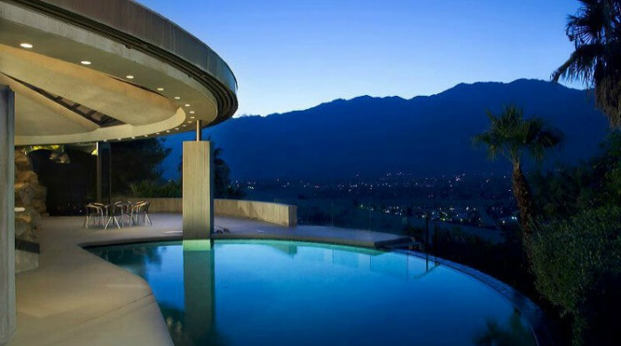 A view of the pool at the Elrod House with the rest of Palm Springs below lit up at night and the sunset disappearing behind mountains.