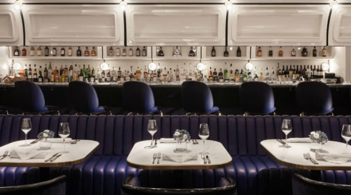 A view of the bar inside Foxglove, Hong Kong with white walls and purple seating.