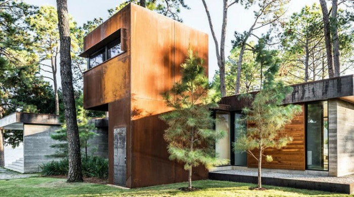 An exterior shot of part of the CCR1 Residence featuring pre-rusted steel walls surrounded by trees.