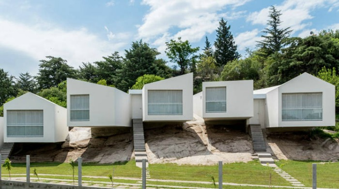 A front view of the Five Houses by Carlos Ciravegna during the day with blue skies and trees behind them.