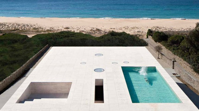 The house of the infinite's roof with a pool and the beach and sea beyond.