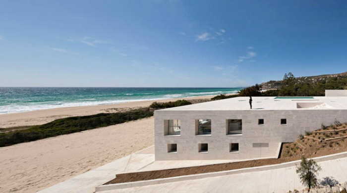 A side view of the house of the infinite showing how it is built into the hill behind it, with views of the beach and sea.