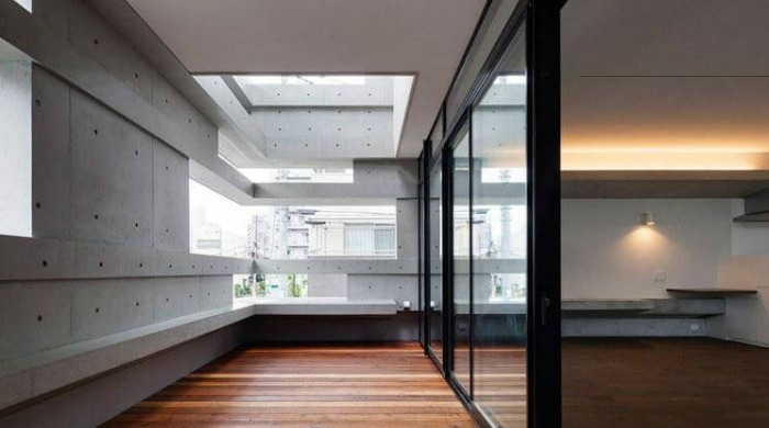 Inside the cranks house by Hugo Kohno with wooden flooring and open spaces in the exterior concrete walls.