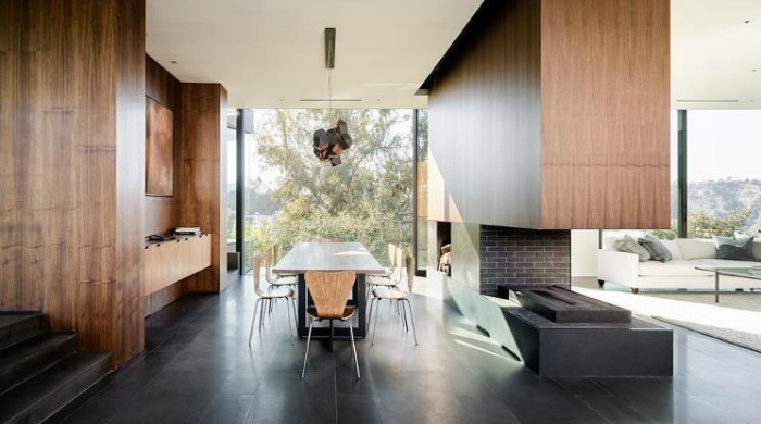 The dining room and open plan living room area in Oak Pass House with wooden walls and floor to ceiling glass windows.