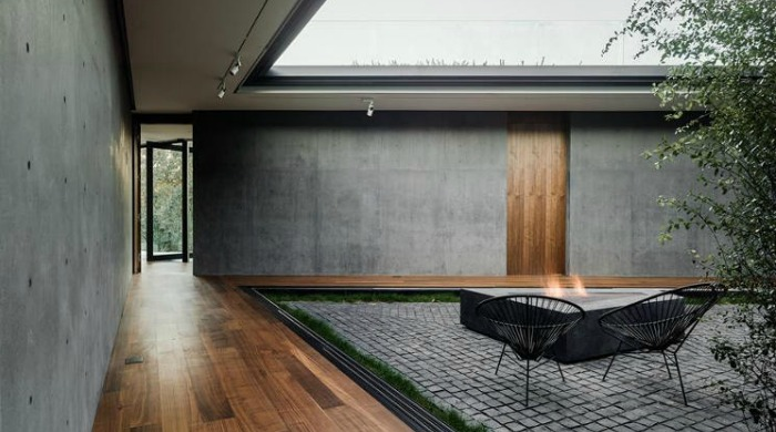 An outdoor seating area with a fire pit in a courtyard at Oak Pass House.