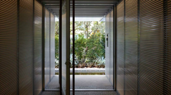 The view down a corridor leading outside from a minimal Miami beach house.