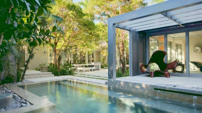 The pool area and courtyard with trees of a minimal Miami beach house.