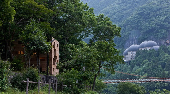 A view of the trees and large bridge surrounding Sou Fujimoto's Wooden House.