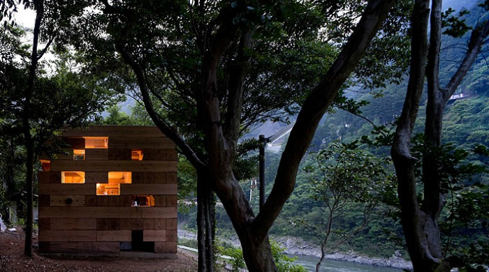 Sou Fujimoto's Wooden House lit up from the inside amidst a dark forest.