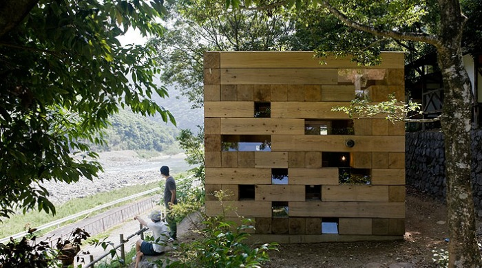Two men looking at the view infront of Sou Fujimoto's Wooden House.