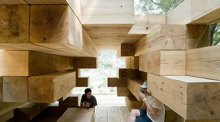 The inside of Sou Fujimoto's Wooden House with two people sat amongst the wooden structure.