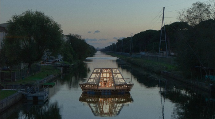 The Jellyfish Barge floating on a river and lit up at night.