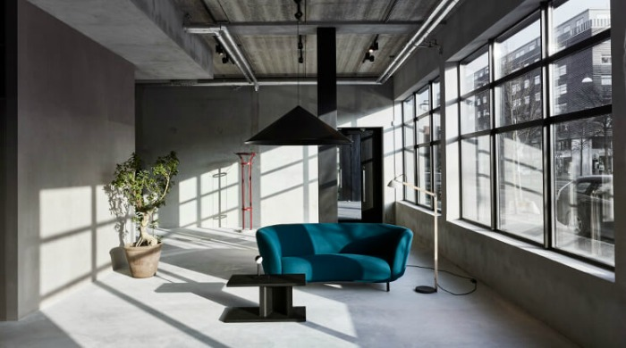A concrete room in an industrial building set up by Massproductions with a large potted plant, turquoise sofa, standing lamp, black table and large black hanging lamp at the Stockholm Furniture and Light Fair 2016.