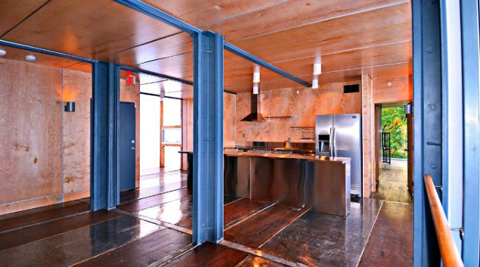 The inside of one of the shipping container apartments with steel columns, wooden flooring and ceilings, and a modern kitchen.