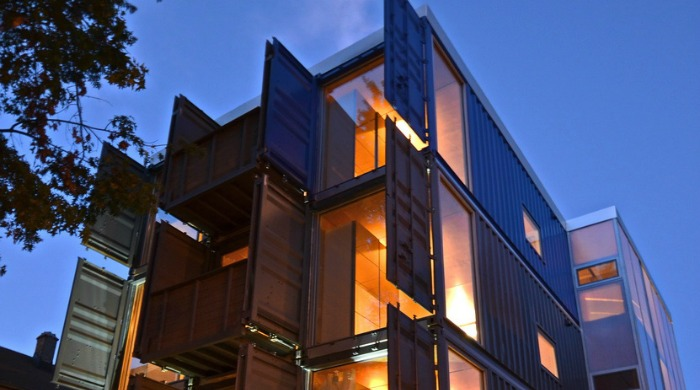 The outside of the shipping container apartments lit up at night, with their doors open to reveal windows.