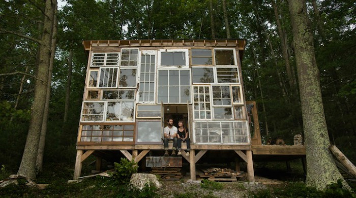 Nick Olson and Lilah Horwitz in their completed glass cabin home in the woods.
