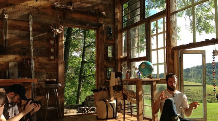 Nick Olson sat inside the glass cabin with views onto the countryside out of the main glass window made out of many smaller windows.