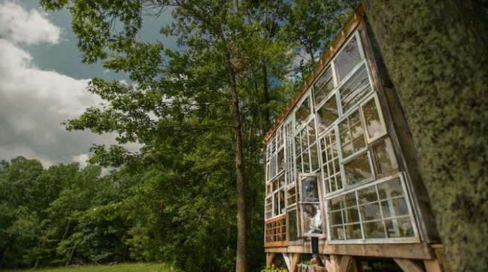 A view of the glass cabin showing the main square glass window made up of many smaller windows surrounded by trees.