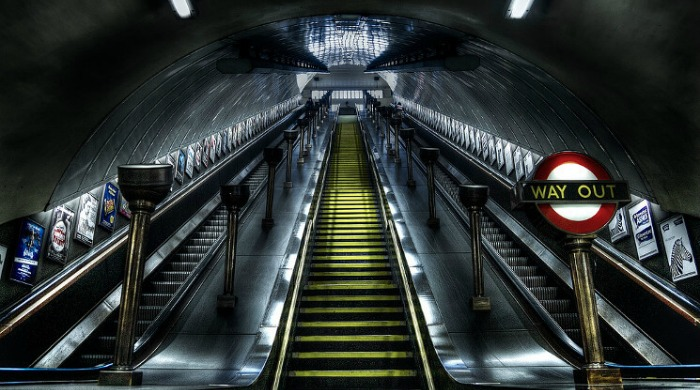 An empty escalator with a red and white way out sign lit up at night in the London Underground series by Mark Cornick.