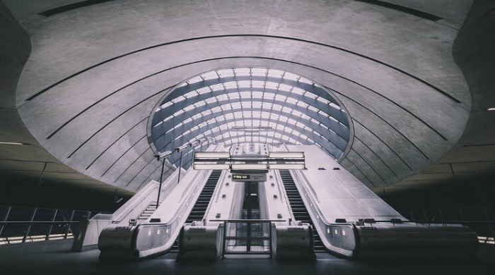 An empty set of escalators lit up at night in the London Underground series by Mark Cornick.
