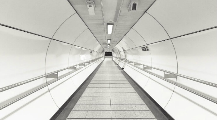 An empty pedestrian tunnel lit up brightly by white lighting in the London Underground series by Mark Cornick.