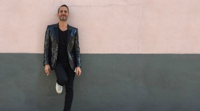 Marc Jacobs leaning against a wall.