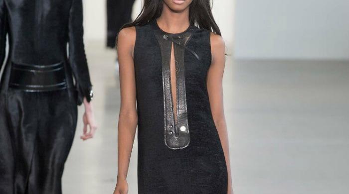 A model on a catwalk wearing a Calvin Klein dress.