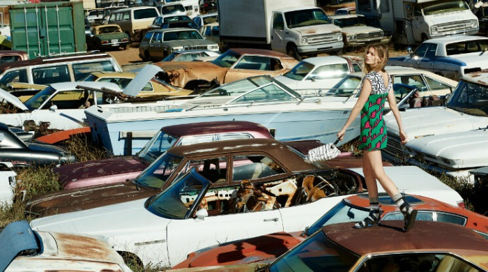 A model wearing KENZO on the roof of an old car.