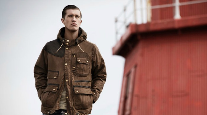 A male model wearing Barbour x White Mountaineering clothing.