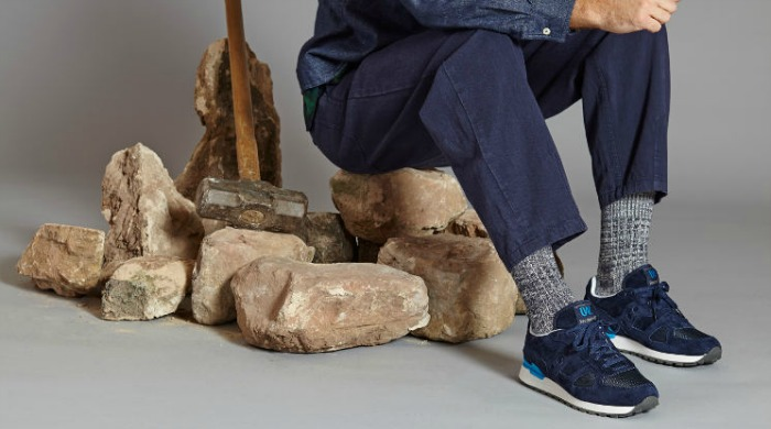 A model wearing blue Saucony Originals x Universal Works trainers.