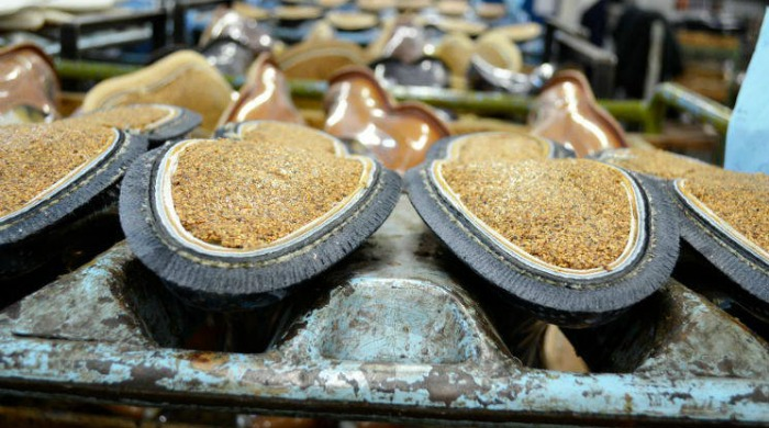 Cork being added to the bottoms of shoes at the Tricker's factory.