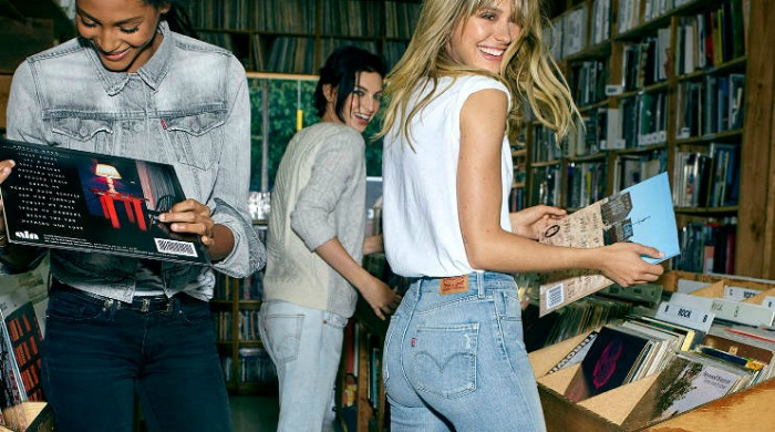 Three models in a record shop wearing Levi's jeans.