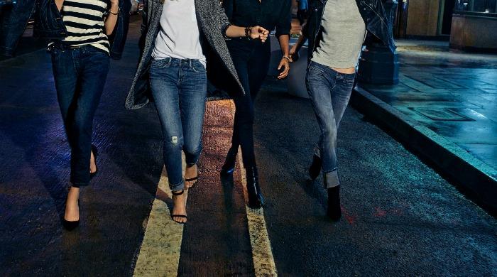 Four models wearing Levi's jeans.