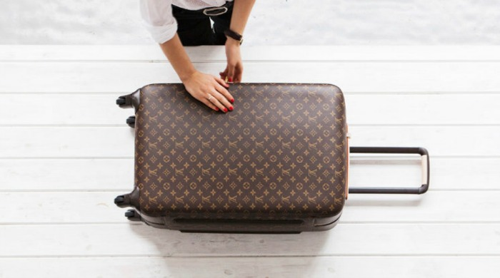 A blogger with a suitcase from her guide on how to pack for a week away.