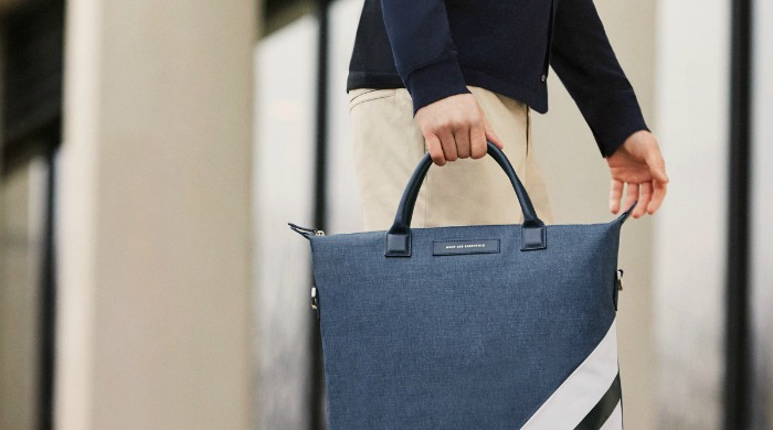 A male model carrying a Want Les Essentiels bag.