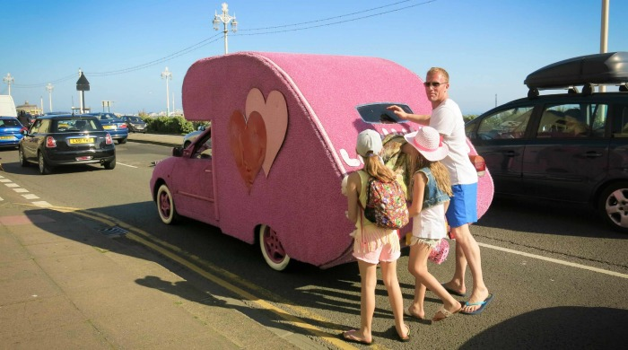 Tourists with a pink car from the 'It's a Brighton Thing' series by Azzurra Biagi.