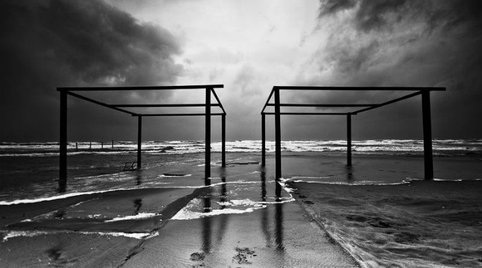 A beach with a geometric structure in black and white by Guy Cohen.