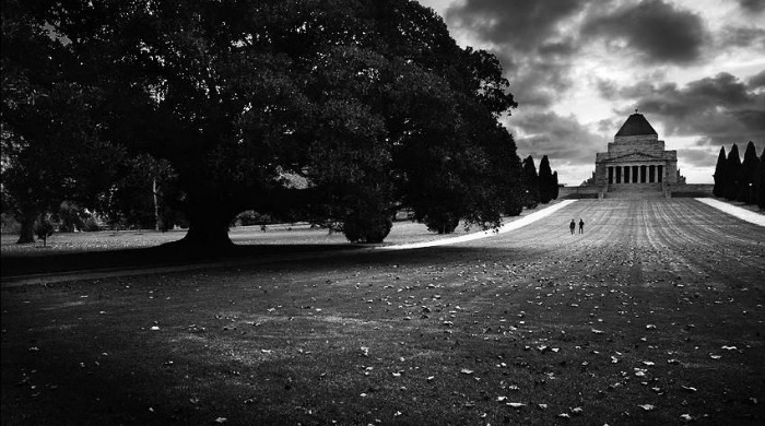A lawn leading up to a building in black and white by Guy Cohen.
