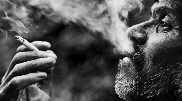 An old man smoking in black and white by Guy Cohen.