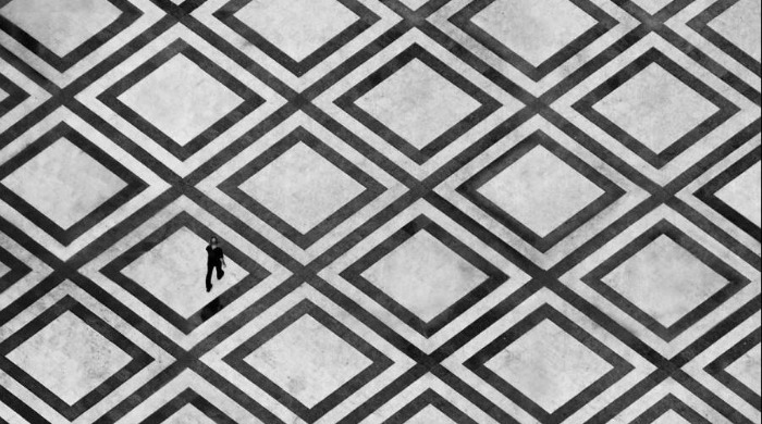 A person walking across a patterned floor in black and white by Guy Cohen.