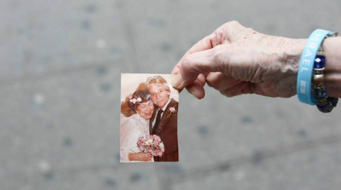 An aged hand holding a wedding photograph from Humans of New York.