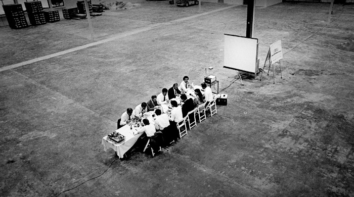 Steve Jobs and the NeXT board of directors at a small table in a large room by Doug Menuez.
